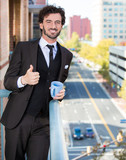 Businessman enjoying cup of coffee on balcony of his apartment