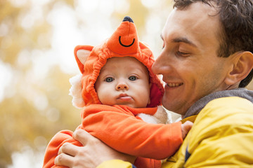Young man and his little son in fox costume in autumn park