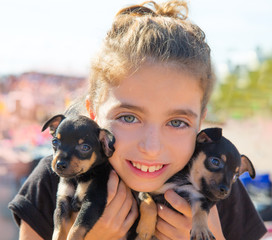 kid girl playing with puppy dogs smiling