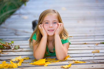 Kid girl in autumn wood deck with yellow leaves outdoor