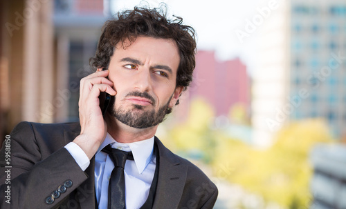Businessman talking on a phone, on a balcony of his apartmentt