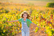 kid farmer  girl running in vineyard field in autumn