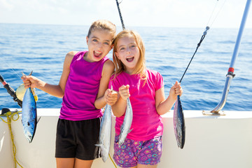 Happy tuna fisherwomen kid girls with fishes catch