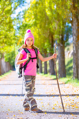 hiking kid girl with walking stick and backpack in autumn