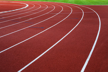 White lines on red running track with green grass.