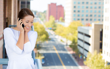 Business woman talking on a cell phone on a balcony of apartment