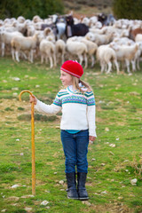 Kid girl shepherdess happy with flock of sheep and stick