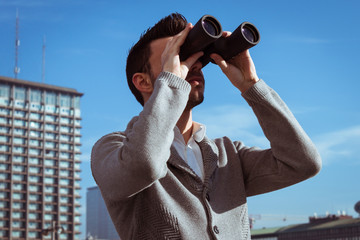 Portrait of a handsome young man looking through binoculars
