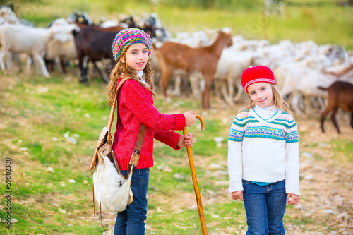 Kid girl shepherdess sisters happy with flock of sheep and stick