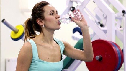 Young woman trains at a gym (drinking water)