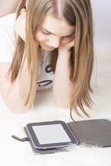 Little teenage girl with e-book at home