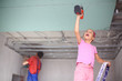 girl with fasten drywall, man is working with profile
