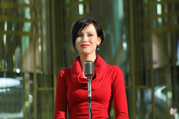 The woman in red standing on stage with microphone
