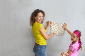 Mother and daughter keep the finishing tile on wall