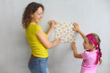 Mother and daughter try on finishing tile on the wall