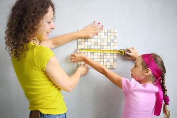 Mother and daughter measuring size of finishing tile