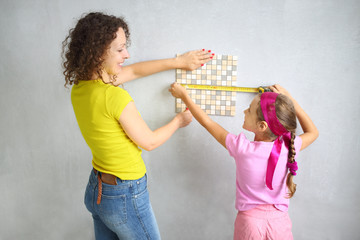 mother and daughter measuring the size of finishing tile
