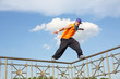A man stands on a thin fence during breakdancing