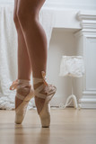 female legs in pointes stand on tiptoe in the studio