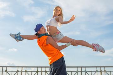 guy holding girl in beautiful pose and girl do splits.