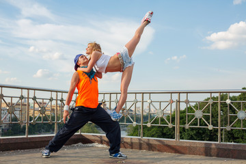 Young pair dancing modern dance in the street