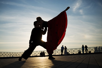 couple dancing on street against sunset
