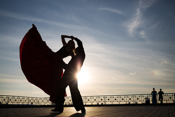 Silhouette of couple dancing on street against sunset