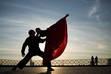 beautiful couple dancing on street against the sky