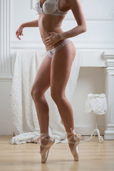 female body standing on tiptoe in lacy lingerie and pointe