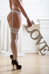 female body in lacy lingerie with stockings holding word Love
