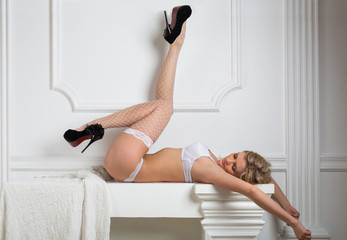 Beautiful girl in lace lingerie and stockings and shoes lying