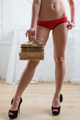Beautiful female body in red lacy lingerie stand stack of book