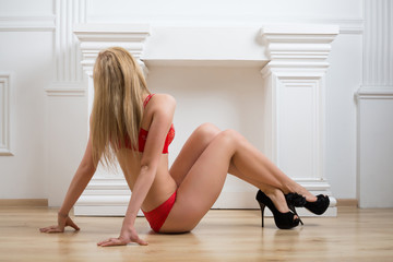 Beautiful girl in lingerie sitting back on floor in studio