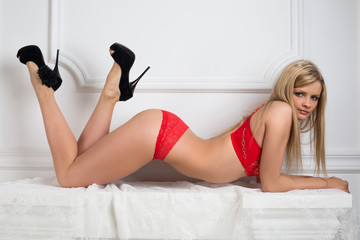 Beautiful girl in red lace lingerie lying in the studio