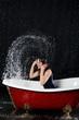 Wet girl have fun in bathtub under the spray of water