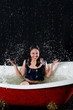 Smiling girl with closed eyes splashes water in bathtub