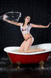 girl in swimsuit is protected against water jets in bathtub