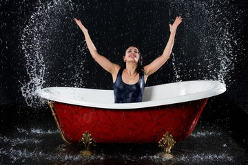 Drenched girl splashes water in bathtub under spray