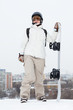 girl snowboarder in helmet stands on hill with snowboard