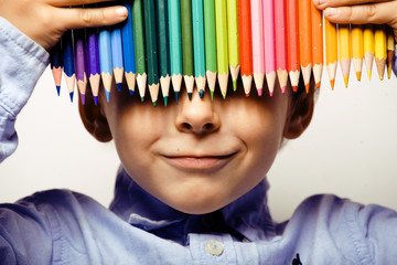 Little cute boy with color pencils close up smiling on white bac