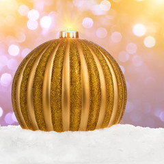 Big golden Christmas ball on snow against festive background