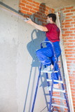 worker on ladder in workwear makes repairs wall poster