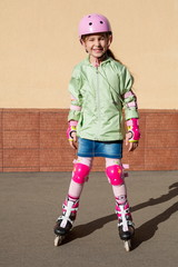 Girl in helmet and protection riding roller skates