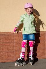 Little girl in helmet and protection riding roller skates
