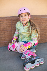 Girl in helmet and protection of hands and feet sit