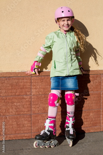 Little girl in helmet and protection riding roller skates