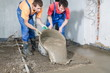 construction workers pour out mortar of cement from bucket