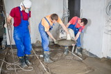 Three workers pour out mortar of cement from bucket