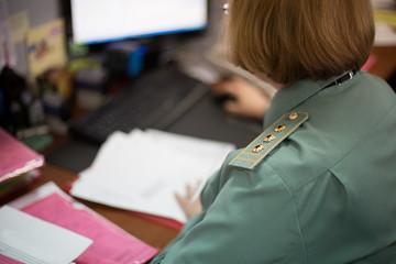 Senior lieutenant in uniform working in office
