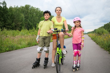 Active rest of family with with roller skates and bicycle